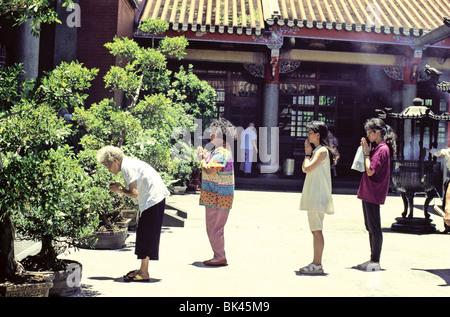 Gläubige in-Line in einem taiwanesischen Tempel mit ein Weihrauch-Brenner im Hintergrund - die meisten taiwanischen - Stockfoto