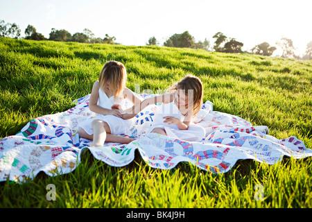 Mädchen auf der Picknickdecke kitzeln einander - Stockfoto