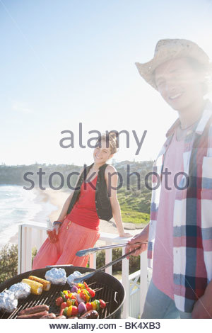 Mann und Frau tendenziell Grill mit Meer im Hintergrund - Stockfoto