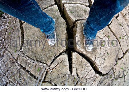 Während einer Dürre Wüste auf trockener, rissiger Boden in einem trockenen Bachbett stehende Person. - Stockfoto