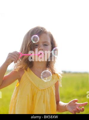 Junges Mädchen im gelben Sommerkleid, Seifenblasen - Stockfoto