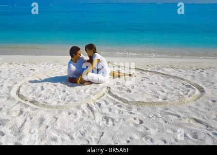 Junges Paar am Strand sitzen in einer herzförmigen Aufdruck auf dem Sand, Malediven, Indischer Ozean, Asien - Stockfoto