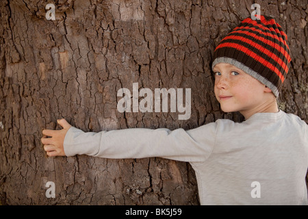 Jungen tragen Mütze Baumstamm umarmen - Stockfoto