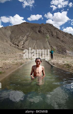 Junge, Bad in einem Bach, Tibet, - Stockfoto