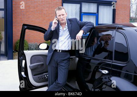 Business-Mann außerhalb sprechen am Handy stützte sich auf sein Auto; zuversichtlich professionelle Anzug - Stockfoto