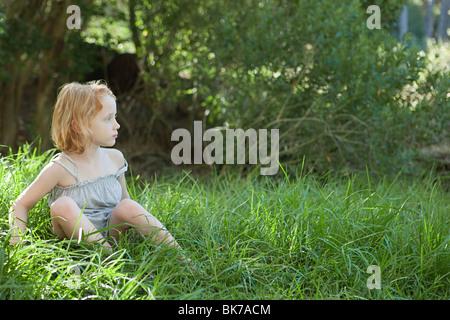 Kleines Mädchen sitzt im Rasen - Stockfoto
