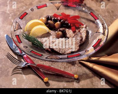 Kaltes Rindfleisch und Oliven und Paprika auf einem geometrischen dekorierten Teller mit roten Besteck auf Stein - Stockfoto
