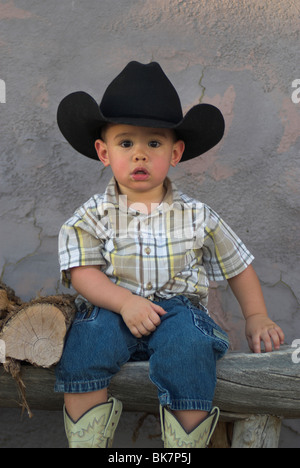 Eine niedliche 2-4 jährige Mischlinge junge einen Cowboy-Hut und sitzt auf einem bench(Released) - Stockfoto