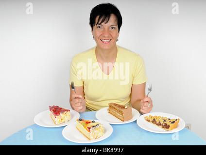 Frau sitzt gerne vor vier Platten mit Kuchen - Stockfoto