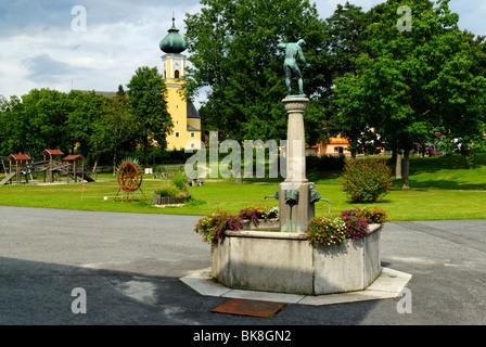 Glasbläser Brunnen vor der Pfarrei Kirche Maria Himmelfahrt, Kirche der Jungfrau Maria, Frauenau, Bayerischer Wald, - Stockfoto
