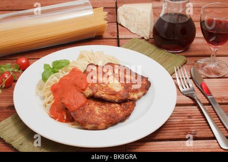 2 Mailänder Türkei Steaks auf Spaghetti mit Tomaten-Sugo, Karaffe und Glas Rotwein, Stück Parmesankäse, Spaghetti - Stockfoto