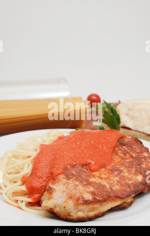 Mailänder Putensteak auf Spaghetti mit Tomaten-Sugo, Stück Parmesankäse, Spaghetti in Glas - Stockfoto