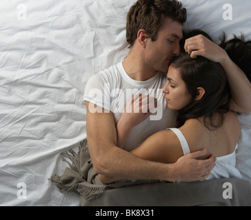 Junges Paar im Bett umarmt - Stockfoto