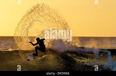 Eine Surfer ist von der Sonne am Krempen Ness in der Nähe von Thurso, Schottland Silhouette. Die Sonne geht im Norden - Stockfoto