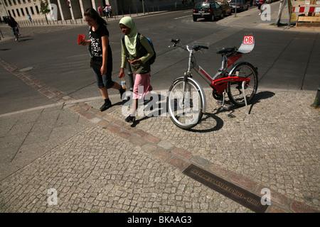Junge muslimische Mädchen, die die symbolischen Trennungslinie an der Stelle, wo die Berliner Mauer in Berlin, Deutschland - Stockfoto