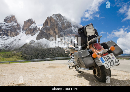 Ein Motorrad auf dem Gipfel des Sella Joch pass in den italienischen Dolomiten mit Blick auf die Berge hinter - Stockfoto