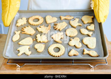 Koch hält Cookie Tablett mit frisch gebackene hausgemachte Spritzgebäck - Stockfoto