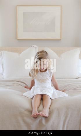 Mädchen sitzen auf Bett, Blick auf ihre Füße - Stockfoto