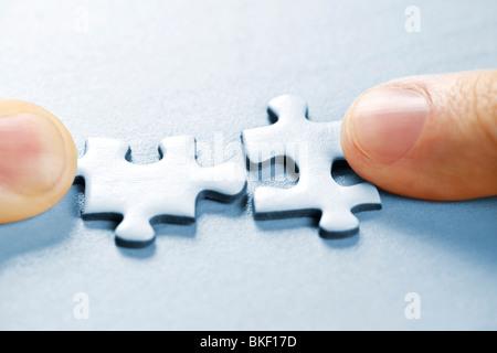 Zwei Puzzlestücke passen zusammen Stockfoto, Bild