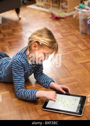 Kind am Boden des Wohnzimmers mit Apple iPad Touchscreen-Computer zu spielen. Ihr Name ist Irene. - Stockfoto