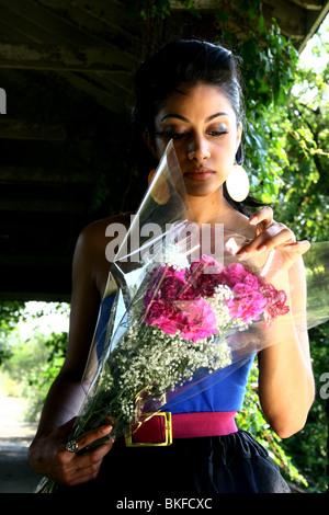 Porträt einer schönen aussehende Süd-asiatisch-amerikanische Frau mit Blumen. Stockfoto