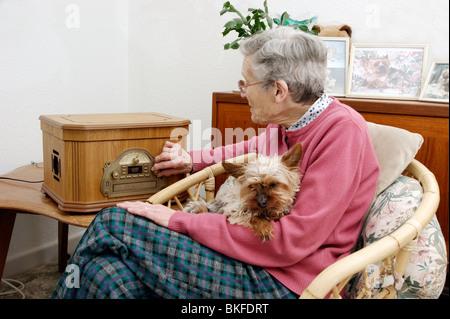 ältere Frau, die Einstimmung auf hören Radio mit ihrem Haustier Hund (analoge Übertragung innerhalb von ein paar - Stockfoto