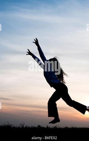 Young Girl energetisch Spaß springen und laufen herum. Silhouette - Stockfoto