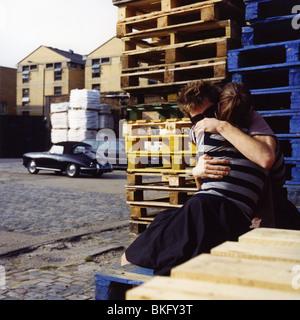 junges Paar umarmt auf Parkplatz mit leeren Kisten und ein schickes altmodisch-Auto im Hintergrund - Stockfoto