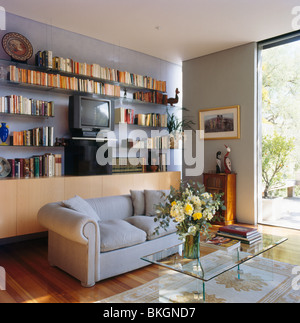 Bücherregale an Wand hinter grauen Sofa in kleinen modernen grauen Wohnzimmer mit Couchtisch aus Glas - Stockfoto