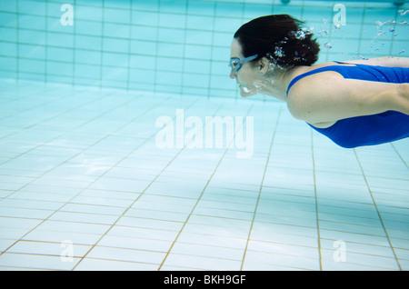 Frau in blauen Badeanzug schwimmen unter Wasser im pool