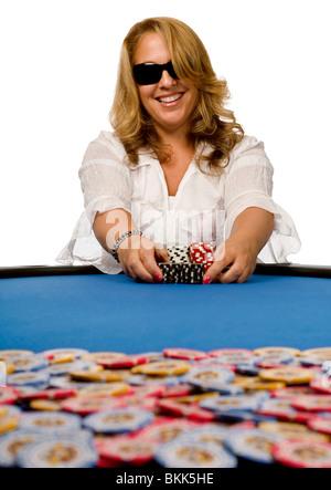 Attraktive blonde Frau schiebt Pokerchips in Richtung Topf auf blauem Filz Tisch. - Stockfoto
