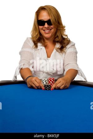 Attraktive Frau drückt ihre Pokerchips nach vorne auf einem blauen Filz Pokertisch. - Stockfoto