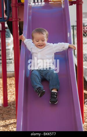 Ein kleiner Junge die Rutsche hinunter - Stockfoto