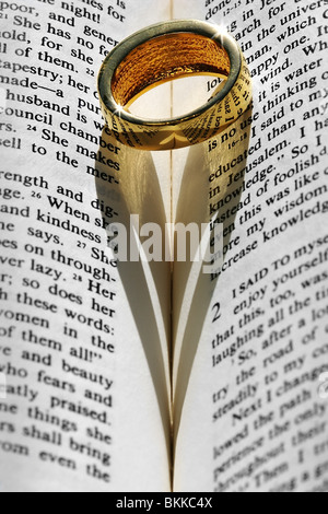 Trauring am Bibel mit herzförmigen Schatten - Stockfoto