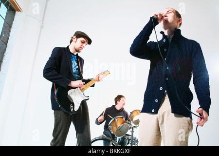 Eine Band mit Sänger, Schlagzeuger und e-Gitarrenspieler - Stockfoto