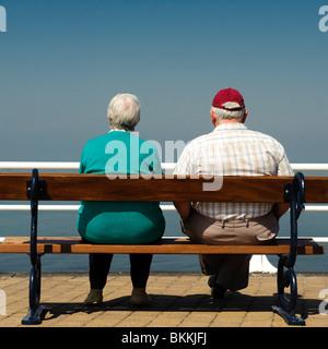 Rückansicht einer älteren älteres paar Mann Frau sitzt auf der Bank am Meer, Sommernachmittag, UK - Stockfoto
