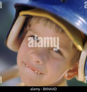 Nahaufnahme eines kleinen Jungen mit einem Basball Teig Helm - Stockfoto