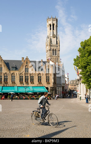 Radfahrer kreuzen Burgplatz in Brügge in Belgien mit dem Glockenturm im Hintergrund - Stockfoto