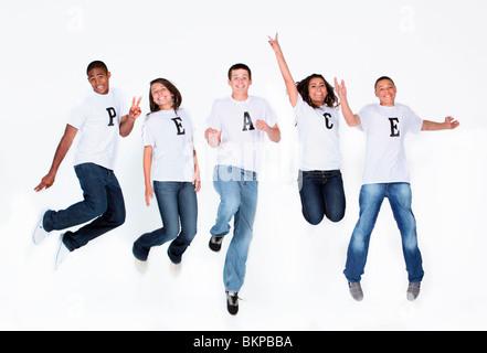 """Eine Gruppe von Jugendlichen springen In die Luft mit ihre T-Shirts Rechtschreibung """"Frieden"""" - Stockfoto"""