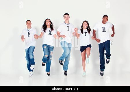 """Eine Gruppe von Jugendliche Holding Hände und springen In der Luft tragen T-Shirts mit The Message """"glauben"""" - Stockfoto"""