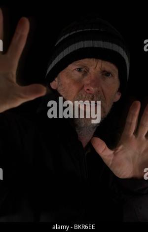 Reifer Mann hält seine Hände gegen Bedrohung. Isoliert. - Stockfoto