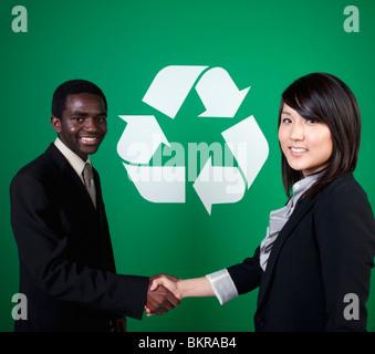 Zwei Geschäftsleute Händeschütteln vor ein Recycling-Symbol - Stockfoto