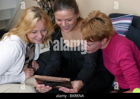 Drei Freundinnen, die gerne mit Blick auf Bild im Bilderrahmen - Stockfoto