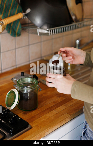 Frau in der Küche, die Zubereitung von Kaffee - Stockfoto