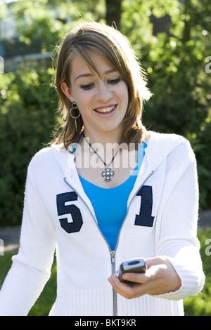 Teenager-Mädchen lesen SMS vom Handy - Stockfoto
