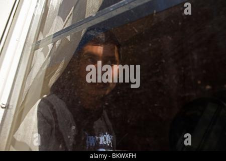 Ein Undocumentd zentralamerikanischen Migrant, Reisen in Mexiko, in den USA arbeiten schaut durch ein Fenster in - Stockfoto