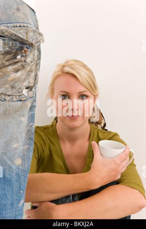 Frau gegen weiße Wand hält eine Kaffeetasse mit Mann Bein tragen schmutzige Jeans neben ihr sitzt - Stockfoto