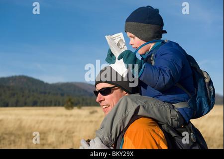 Ein kleiner Junge fängt eine Fahrt auf seines Vaters Schultern beim Kartenlesen. - Stockfoto
