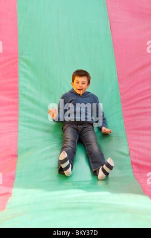 Ein MODEL Release Bild eines jungen auf einer Folie Wroxham Scheunen Jahrmarkt in Wroxham, Norfolk, England, Großbritannien, - Stockfoto