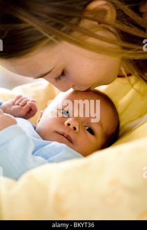 Mädchen küssen Neugeborenen Stiefbruder - Stockfoto